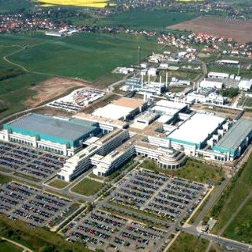 In der Luftaufnahme sind die zwei großen Module 1 und 2 sowie das Gebäude »Bump und Test« (ganz rechts) zu erkennen. Im Hintergrund sind zwei eigene Kraftwerke zu sehen, die mit ihrer Kapazität theoretisch ganz Dresden mit Energie versorgen könnten.