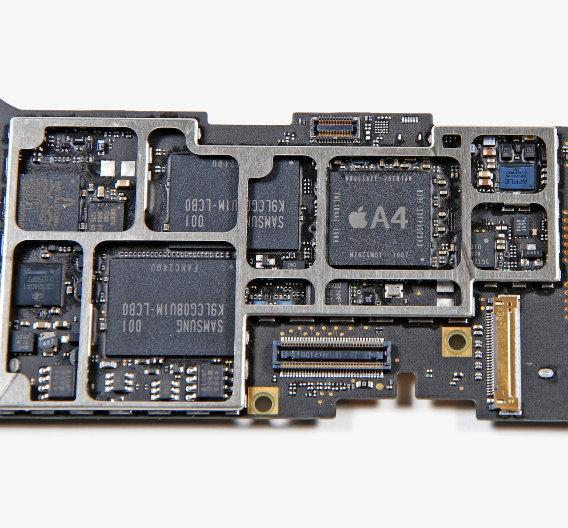 Herz und Nieren des iPad: Mittig der A4-Prozessor von Apple im »Package on Package« mit zwei DRAM-Dies von Samsung. Mitte links die beiden MLC-NAND-Flash-Speicher-Chips mit jeweils 8 GB von Samsung.  Weitere Komponenten:  Broadcom: BCM5973 I/O Controller Texas Instruments: CD3240A1 NXP: L061 01 4 ZSD950
