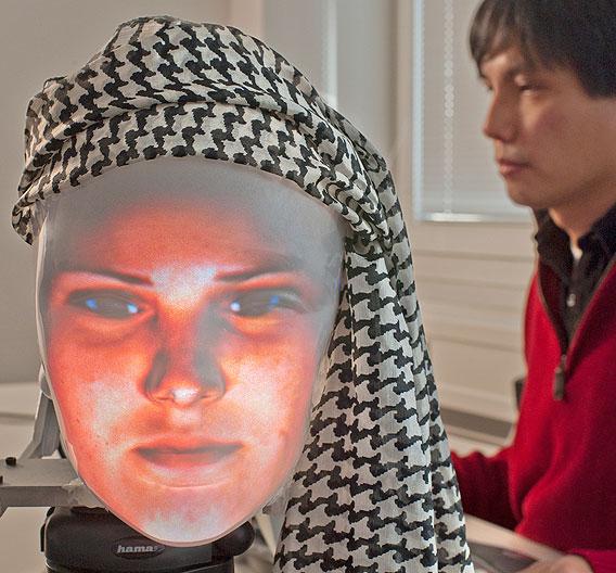Ein besonders starker, kleiner Beamer sowie eine spezielle Leuchtschicht-Imprägnierung auf der Innenseite der Kunststoffmaske verhelfen Mask-Bot obendrein zu so viel Leuchtkraft, dass die Kommunikation Mensch-Maschine auch bei Tageslicht möglich ist.