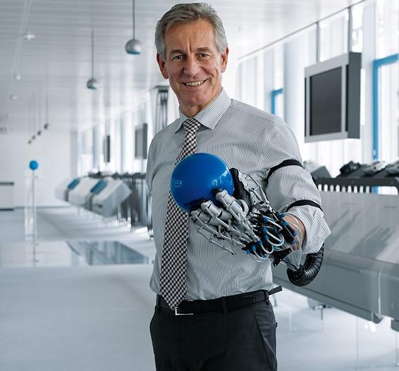 Wie gut die »ExoHand« die menschliche Hand dabei unterstützen kann, Gegenstände wie einen Ball zu halten, demonstriert hier der Festo-Vorstandsvorsitzende Dr. Eberhard Veit.