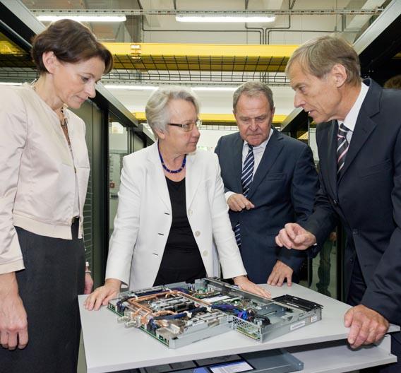 Prof. Bode und Frau Koederitz erläutern an einem geöffneten Knoten des SuperMUC die Kühlung mit warmem Wasser.