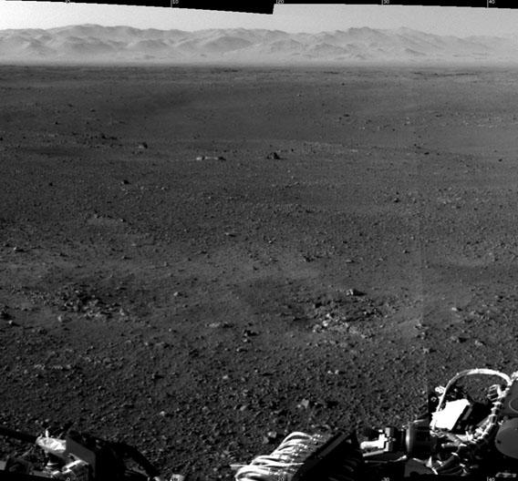 Zwei zusammengefügte hochauflösende Bilder der Curiosity-Landestelle. Deutlich im Vordergrund zu sehen sind die Abdrücke im Untergrund, die durch die Düsen bei der Landung der Sonde entstanden sind. Die Bilder wurden mit der Kamera aufgenommen, die auf dem Mast der Sonde sitzt. Im Hintergrund sind die Ränder des Gale-Kraters zu sehen, in dem sich Curiosity gerade befindet.