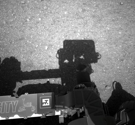 Die erste Aufnahme der Navigatiosnkamera von Curiosity. Deutlich zu sehen ist der Schatten, den die auf einem Mast sitzende Kamera wirft. Diese Navigationskamera ist dazu da, um die Position der Sonne zu finden, was für die Navigation benötigt wird. Für das Foto hat sich die Kamera um 180 Grad gedreht, nachdem sie in die Sonne gerichtet war.