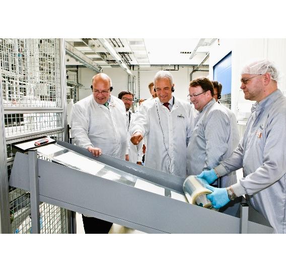 Bundesumweltminister Peter Altmaier und Ministerpräsident Stanislaw Tillich beobachten interessiert die Produktion der Solarfolien