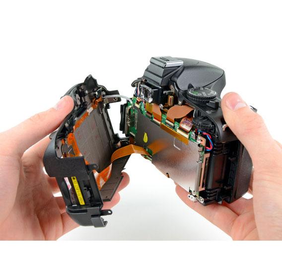 Bild 2: Nach ungefähr 20 Schrauben lässt sich die Rückseite der Kamera abnehmen.  Rückseite und Kamera sind dabei mit zwei Kabeln verbunden. Über das Rundkabel werden die Informationen der Knöpfe auf der Rückseite an die Kamera geschickt. Über das 40-polige Flachbandkabel erfolgt die Datenübertragung zwischen Kamera und dem LC-Display auf der Rückseite. <a href=