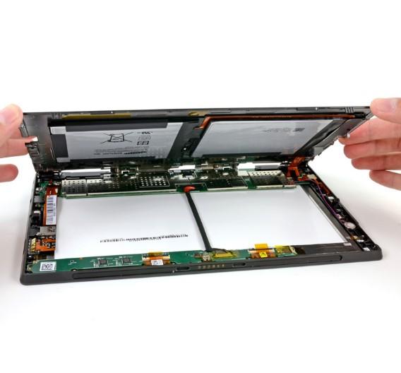 An das Innenleben des Surface-Tablets zu gelangen, ist zunächst recht mühsam: Insgesamt 17 Torx-Schrauben halten das Gehäuse zusammen.  Sind diese gelöst, hängt der rückseitige Gehäusedeckel nur noch an einem flachen Kabel, das die Batterie mit dem Motherboard verbindet.   <a href=
