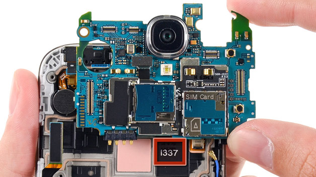 Eine Schraube und mehrere Verbindungsstücke sind zu entfernen, um das Herzstück des S4, das Motherboard freizulegen. Beim Herauslösen fällt auf, dass Samsung dem fachkundigen Bastler hier verschlüsselt mitteilt, was man vom eigenen Gerät hält: Die Zahl 1337 steht für das Wort LEET, was soviel heißt wie »Elite«.  <a href=