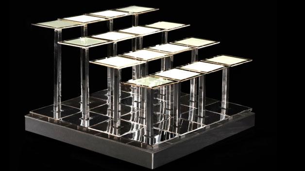 Und so sieht ein Modul aus: es besteht aus einem ca. 3m x 3m großen Basismodul. In das Basismodul kommen Glasröhren verschiedener Längen, auf denen wiederum die OLED-Module sitzen. Die Länge der Glasröhren ist variabel, so dass sich die unterschiedlichsten Formen erzeugen lassen. Die einzelnen OLEDs sind dabei 7,6 cm x 7,6 cm groß, haben eine Farbtemperatur von 3000 K und eine Helligkeit von 1500 cd/m².