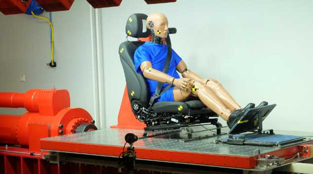 Der angestrahlte Schlitten auf dem Compact-Impact-Simulator kurz bevor der Kolben den Whiplash Test auslöst