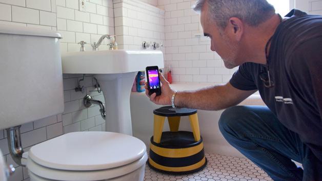 Die erste iPhone Wärmebildkamera FLIR One liefert einem Handwerker Daten über Energieeffizienz von Wohnungen