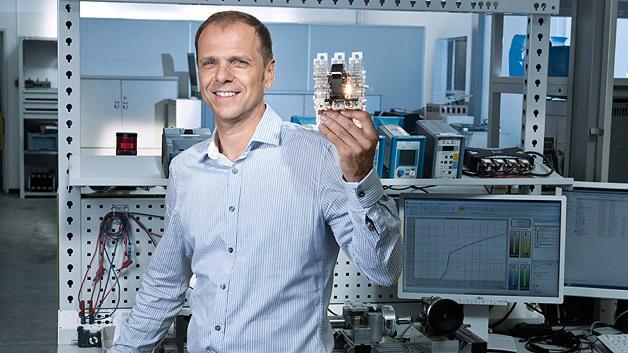 Überall, wo Strom in Niederspannungsnetzen verteilt werden muss, regeln Leistungsschalter, welche Netzteile im Falle eines Kurzschlusses in Betrieb bleiben. Damit diese Schalter zuverlässig arbeiten, ist ausgeklügelte Mechanik gefragt. Jörg-Uwe Dahl arbeitet für die Division Energy Management in Berlin und hat beispielsweise einen Schalter mit einem platzsparenden Rotor erfunden, der zuverlässig und mit sehr geringem Stromverlust Kontakte herstellt sowie robuster ist als Vorgängermodelle.