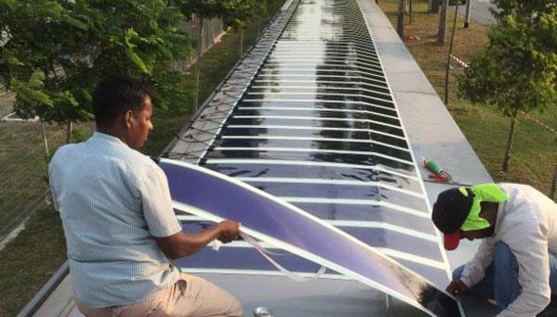 Organische Solarfolie des Dresdner Unternehmens Heliatek wird auf dem überdachten Gehweg nahe des Militärflughafens in Singapur installiert.