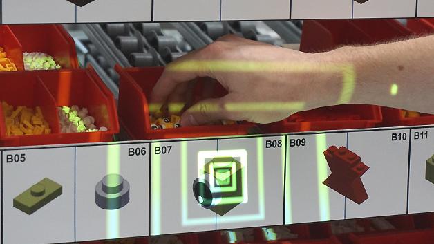 ((Hilfe für den Monteur: Die mobile Projektion zeigt dem Bediener eines Handarbeitsplatzes an, welches Teil er wo greifen muss.))