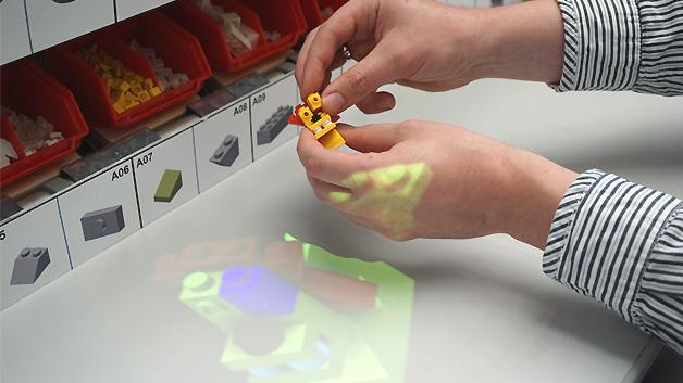 ((Ein 3D-Modell mit der Montageanleitung wird auf den Handarbeitsplatz projiziert und leitet den Mitarbeiter Schritt-für-Schritt durch die Montage.))