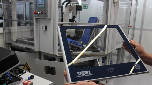 Ein Roboter (Hintergrund) erledigt die saubere Verklebung von Displayglas und –rahmen. Hier ein Touch-Monitor für die medizinische Endoskopie.