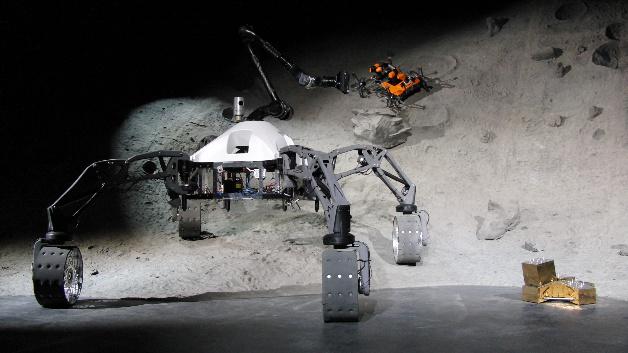 Die mobilen Systeme SherpaTT (links), Coyote III (hinten im Krater) und die Basistation mit aufgestecktem Nutzlastmodul (rechts) bilden eine logistische Kette.