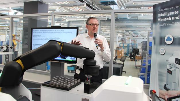 Im APAS-Showroom: Wolfgang Pomrehn, Produktmanager der APAS-Familie von Bosch, stellt die drei Modelle der Produktfamilie vor. Der Roboterarm »Assistant« stand bereits auf der Automatica 2016 im Mittelpunkt, daher wird auf der Vision die meiste Aufmerksamkeit ...