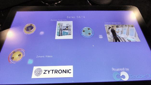 Zytronic präsentiert die Fähigkeiten seiner neuesten Objekterkennungstechnologie ObjectViz auf der electronica (Stand A3.319). Die gemeinsam mit Tangible Display entwickelte Objekterkennungsfunktionalität ist selbst für 85 Zoll große Touch-Tische verfügbar und somit wird kameralose Objekterkennung vermutlich erstmals auf Touchscreens dieser Größe ermöglicht. Die Objekte werden dabei mit physischen Markern versehen, wodurch sich eine Modifizierung der Touch-Tisch-Hardware erübrigt.  Ein wesentlicher Vorteil der von Zytronic und Tangible Display gemeinsam entwickelten Technologie ist, dass auf dem Glas abgelegte Stifte oder Taschen sowie Berührungen durch Kleidungsstücke einfach ignoriert werden. Der Controller wird dazu programmiert, nur spezifische, mit einem Objekt verbundene sogenannte Phymarks (physische Marker) zu erkennen und entsprechend zu reagieren. Darüber hinaus wird ein kompletter Bericht sämtlicher Benutzerinteraktionen zur nachfolgenden Prüfung und Auswertung gespeichert.