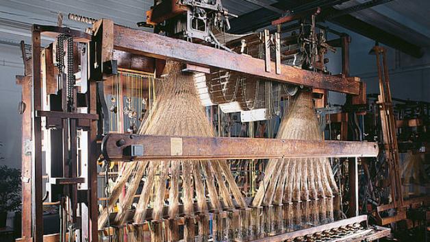 Zu Beginn des 19. Jahrhunderts entwickelt Joseph-Marie Jacquard den mechanischen Webstuhl technologisch weiter. Mit dieser Vorrichtung können Leonische Waren erstmals in großgemusterte Gewebe eingebracht werden.