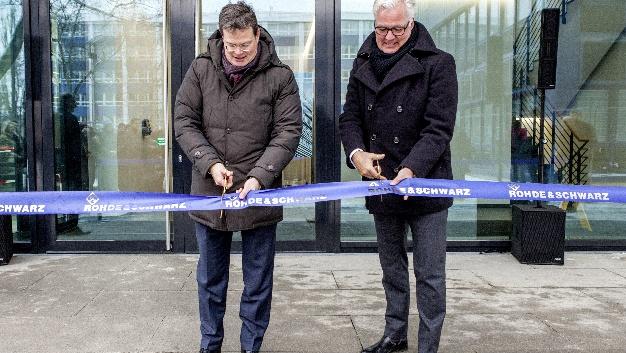 Christian Leicher, Vorsitzender der Geschäftsführung von Rohde & Schwarz, und Stephan Georg Kahl, Geschäftsführer der R&S Immobilienmanagement GmbH, durchtrennen gemeinsam das symbolische Absperrband.