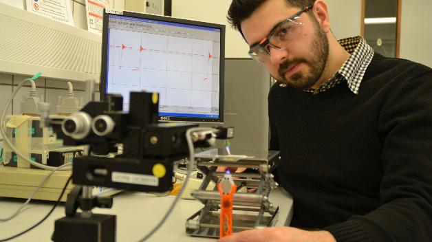 An einem Versuchsaufbau zur Kraftmessung testet Materialwissenschaftler Emre Kizilkan, wie stark das Kompositmaterial an Objekten haftet, wenn es mit UV-Licht bestrahlt wird.
