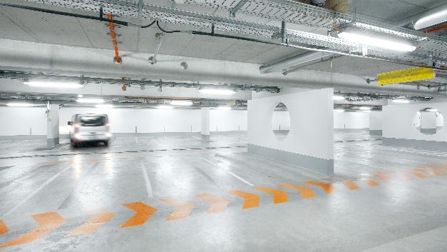 Für maximale Sicherheit für Mensch und Fahrzeug in Parkhäusern sorgt die Siteco-Leuchte Compact Monsun LED Parking von Osram. Sie wartet mit 4500 lm Bemessungslichtstrom und einer optimalen vertikalen Ausleuchtung auf. Ergänzend zur bisher horizontalen bringt die vertikale Ausleuchtung mehr Licht in die Stellplätze und in die Fahrgasse. Personen, die sich im Parkhaus bewegen, sind besser erkennbar – auch durch eine verbesserte Gesichtsausleuchtung und weniger Schattenbildung. Zudem ist die Leuchte mit einem Hochfrequenz-Sensor (HC1) ausgestattet. Er registriert Bewegungen im Umfeld und passt die Beleuchtungsstärke entsprechend an, sobald sich weder Personen noch Fahrzeuge im Parkhaus bewegen. Das Licht wird gedimmt oder ausgeschaltet. Über ein Sensorkit lässt sich die Sensortechnologie auch nachrüsten. Eine weitere Variante der Compact Monsun LED Parking ist mit der Funkverbindung Lightify Pro ausgestattet. Diese erlaubt eine drahtlose Lichtsteuerung, bei der die Leuchten per Funk miteinander kommunizieren und gesteuert werden können. Die Installation einer gesonderten Verkabelung ist nicht mehr nötig.