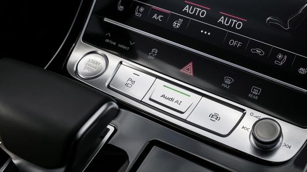 Der Fahrer aktiviert den Staupilot mit der AI-Taste auf der Mittelkonsole.