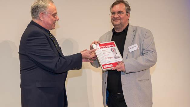 Elektronik-Redakteur Alfred Goldbacher beglückwünscht Wolf-Dieter Roth, der stellvertretend für den Distributor Hy-Power Power Components die Urkunde für den Drittplatzierten Maxwell Technologies entgegennahm.