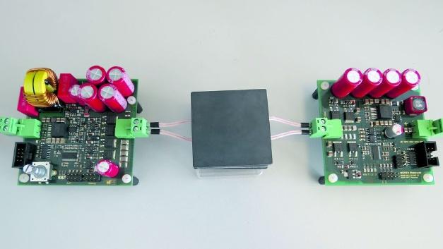 Das Wireless-Power-Entwicklungssystem 760308EMP-WPT-200W, das Würth Elektronik eiSos mit Unterstützung der Infineon Technologies AG entwickelt hat, besteht aus einem Netzteil, einer Sender- und einer Empfängereinheit. Es ist für eine Leistung von bis zu 200W konzipiert und basiert auf Halbleitern von Infineon: Leistungs-MOSFETS, Treiber-ICs, Mikrocontroller und Spannungsregler. Der Sender besteht aus einer MOSFET-Vollbrücke und einem Resonanzkreis, gebildet aus der Serienschaltung von WPT-Spule und den Resonanzkondensatoren. Aufgrund der Phasenverschiebung zwischen Spannung und Strom im Resonanzkreis schaltet der Leistungswandler im Spannungsnulldurchgang (ZVS – Zero Voltage Switching) und ermöglicht so einen hohen Wirkungsgrad. Auf der Empfängerseite wird ein Synchron-Gleichrichter mit nachfolgender Filterung und Siebung eingesetzt. Zusätzlich können durch Amplitudenmodulation des Wechselfeldes zwischen Sender und Empfänger beliebige Daten von der Empfängerseite an die Senderseite übertragen werden.