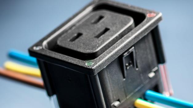 """16-A-IEC-Gerätesteckdose für intelligente PDUs Die 16-A-Gerätesteckdosen der Serie 4710-5 von Schurter verfügen über integrierte Führungen für Lichtleiter. Bis zu vier optional erhältliche Lichtleiter lassen sich dabei über LEDs auf der Leiterplatte einsetzen. Die Ansteuerung der LEDs ist frei konfigurierbar. Um einem Schaden vorzubeugen, sind die Lichtleiter als notwendiges Zubehör zu bestellen und sollen erst nach der Verdrahtung der Dosen in die Verteilerleiste eingesteckt werden. Besonders effizient ist der Einsatz der IDC-Anschlüsse, durch die sich mehrere Dosen in einem Schritt schnell und zuverlässig verdrahten lassen. Für eine individuelle Speisung und Statusindikation ist der Phasenkontakt als Leiterplattenanschluss ausgeführt. Auf Wunsch können diese auch als Steck- oder Lötanschluss konfiguriert werden. Schurter bietet die Steckdosen in Schwarz, Weiss und Grau an. Die Serie 4710-5 ist in zwei Versionen erhältlich: """"along"""" und """"cross"""". Je nach Design der Verteilliste und der Anordnung der Dosen macht es Sinn, mehrere Dosen vertikal (along) oder horizontal (cross) hintereinander zu platzieren. Entsprechend dieser Ausrichtung ist die Orientierung der Anschlüsse. Um nicht ungewollt ein falsches Kabel herauszuziehen, bieten die Dosen das V-Lock Auszugsicherungssystem. Die Schnapp-Montage der 4710-5 ist für Plattendicken von 1,0 bis 3,0mm ausgelegt. Standardausführungen sind in 1,5 und 2,0mm erhältlich. Schurter Electronic Components, Halle B4, Stand 227"""