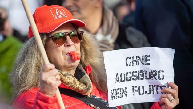 Eine Frau hält ein Schild mit dem Motto der Demonstration: »Ohne Augsburg kein Fujitsu«.