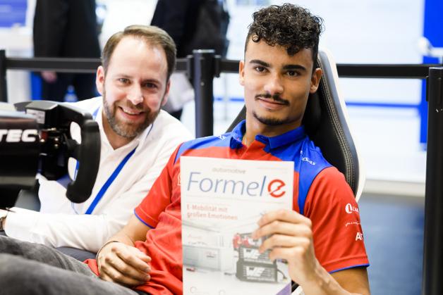 Formel-E-Rennfahrer Pascal Wehrlein am Fahrsimulator auf dem Renesas-Stand, zusammen mit Elektronik-automotive-Redakteur Andreas Pfeffer.