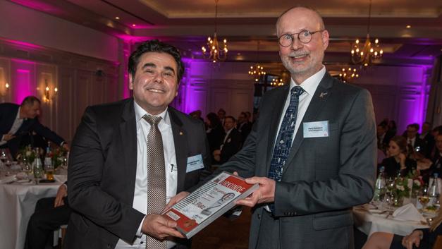 Bernhard Kluschat von TDK-Lambda Germany (links) erhält die Urkunde für den 3. Preis von Harry Schubert, Redakteur der Elektronik, (rechts) für die Netzteilreihe CUS100ME.