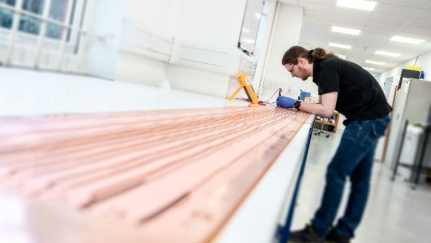 Ein Mitarbeiter von Trackwise prüft die in einem Stück gefertigte flexible Leiterplatte.