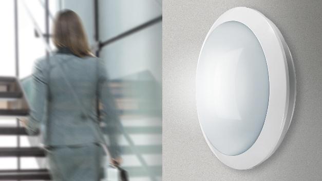Die LED-Wand- und -Deckenleuchten der Serie Alma von Esylux eignen sich besonders für die Modernisierung von Fluren, Treppenhäusern und Foyers in öffentlichen Gebäuden. Eine optional integrierte, unsichtbare Bewegungs- und Lichtsensorik gewährleistet einen energieeffizienten Betrieb, während Schutzart IP65, Stoßfestigkeitsgrad IK10 und eine Nulldurchgangsschaltung für Langlebigkeit sorgen. Die runden Leuchten besitzen einen gewölbten, opalweißen Diffusor, hinter dem sich ein Hochfrequenz-Bewegungsmelder mit integrierter Lichtsensorik verbirgt, der das Licht nur aktiviert, wenn sich Menschen in der Nähe befinden und das vorhandene Umgebungslicht nicht ausreicht. Sein Erfassungsbereich beträgt 360 Grad, die Reichweite 15 Meter im Durchmesser. Die Reichweitet lässt sich ebenso wie Nachlaufzeit und Helligkeitswert über Drehpotis stufenweise den örtlichen Gegebenheiten anpassen. Für eine einfache Vernetzung mehrerer Leuchten besitzen diese eine vorinstallierte Durchverdrahtung über eine Steckklemme. Die Alma-Leuchten sind mit einer Lichtfarbe von mit 3000 oder 4000 K erhältlich bei einer hohen Farbkonsistenz von weniger als 3 MacAdam-Ellipsen. Der Flickerfaktor liegt bei unter 3 %, der Durchmesser der Leuchtengehäuse beträgt 300 mm.