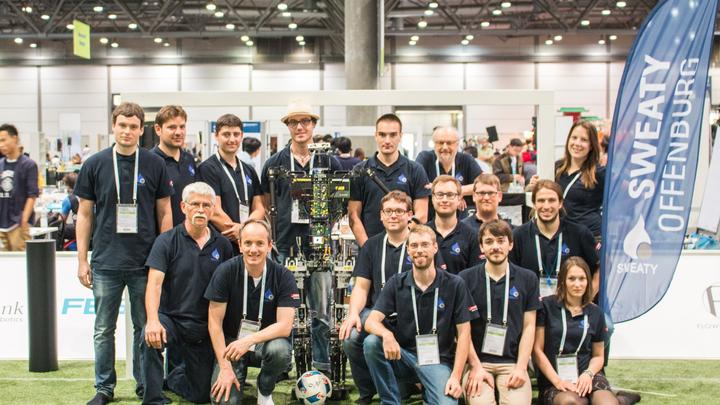 Hochschule entwickelt Hightech-Roboter für die WM 'RoboCup' - Fußballbegeisterung, Pioniergeist und technisches Know-how Ein Team der Hochschule Offenburg arbeitet derzeit an der Weiterentwicklung ihres Fußballroboters 'Sweaty'. 'Sweaty' ist ein Fußball spielender, humanoider Roboter, der erstmals vor zwei Jahren an der RoboCup Weltmeisterschaft in Brasilien teilgenommen hat. Der Name des Roboters ist Programm. Eine der wichtigsten Aufgaben der Entwickler war und ist es, die enorme Wärmeentwicklung des Roboters in den Griff zu bekommen. Denn 'Sweaty' wird warm, sehr warm, soll heißen, er schwitzt. Ins Schwitzen bringen ihn seine komplexen Aufgaben. Sehen, erkennen, analysieren oder bewegen. Eine aufwändige Entwicklungsarbeit. Initiator des Projektes war Prof. Dr. Ing. Ulrich Hochberg. Er wollte für seine Studenten eine Herausforderung schaffen, die Möglichkeit erlerntes Wissen aus dem Studium in der Praxis umzusetzen. Das Team besteht inzwischen aus 3 Professoren, einigen Hochschulmitarbeitern und Studenten der Fakultäten Maschinenbau und Verfahrenstechnik, Elektrotechnik und Informationstechnik sowie Medien und Informationswesen. Über 20 Personen sind mit Begeisterung dabei, einen Roboter zu entwickeln, der bis 2050 den dann amtierenden Fußball-Weltmeister schlagen kann. Durch das Zusammenspiel aller Fakultäten konnte pünktlich zum RoboCup in Brasilien ein erster Protoyp des 'Sweaty' auf das Spielfeld auflaufen. Koordiniertes Arbeiten verschiedener Teams - auch eine Eigenschaft, die, an der Hochschule erprobt, für die Praxis wichtige Erfahrungen bringt. Die Studenten im Projekt sind in drei Teams aufgeteilt und jeweils für eigene Themenschwerpunkte zuständig. Sie arbeiten in den Bereichen Mechanik/Motion, Decision und Vision.  Das Team Motion arbeitet an der Bewegungskoordination und Mechanik des Roboters. Dieser Themenbereich ist äußerst komplex, deshalb ist dieses Team in drei Untergruppen aufgeteilt - IT / Software / Steuern / Rechnen, Mechanik und Elektronik. D