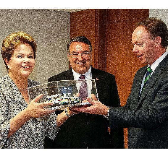 Ian Robertson, Mitglied des Vorstands für Vertrieb und Marketing BMW (rechts) überreicht der brasilianischen Präsidentin Dilma Rousseff (links) in der Hauptstadt Brasilia ein BMW Art Car Modell anläßlich der Ankündigung zu Plänen für ein neues BMW Werk in Brasilien (Mitte: Raimundo Colombo, Gouverneur des Bundesstaats Santa Catarina).