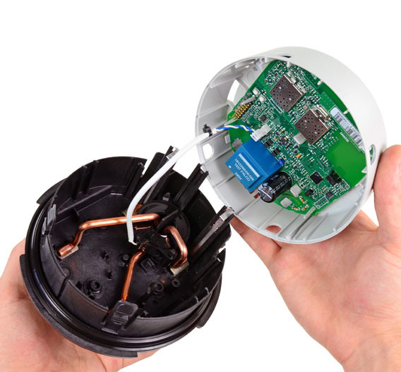 Die beiden Hälften sind mit einem Kabel verbunden, dass wiederum mit einem Steckverbinder auf der Leiterplatte befestigt ist. Links sieht man die dicken Kupferkabel für die Stromversorgung des Gerätes, die bis zu 200 A vertragen. Dadurch lässt sich das Smart Meter direkt an die Stromversorgung des Hauses anschließen.