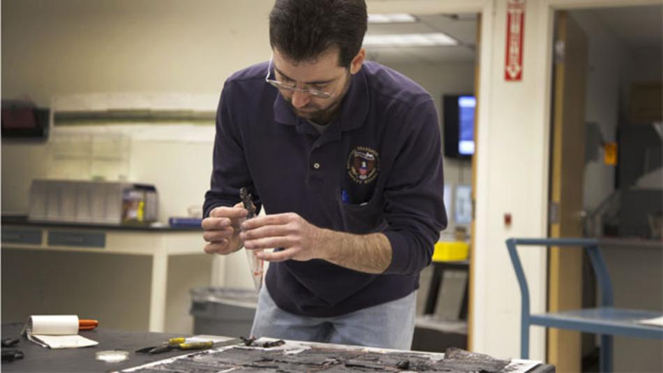 Ein NTSB-Mitarbeiter dokumentiert Einzelteile aus dem verbrannten Akku. Der Grad der Zerstörung erschwert es, die Ursache für den Brand zu finden. Im Inneren des Akkus herrschten Backofen-Temperaturen von über 260 °C.
