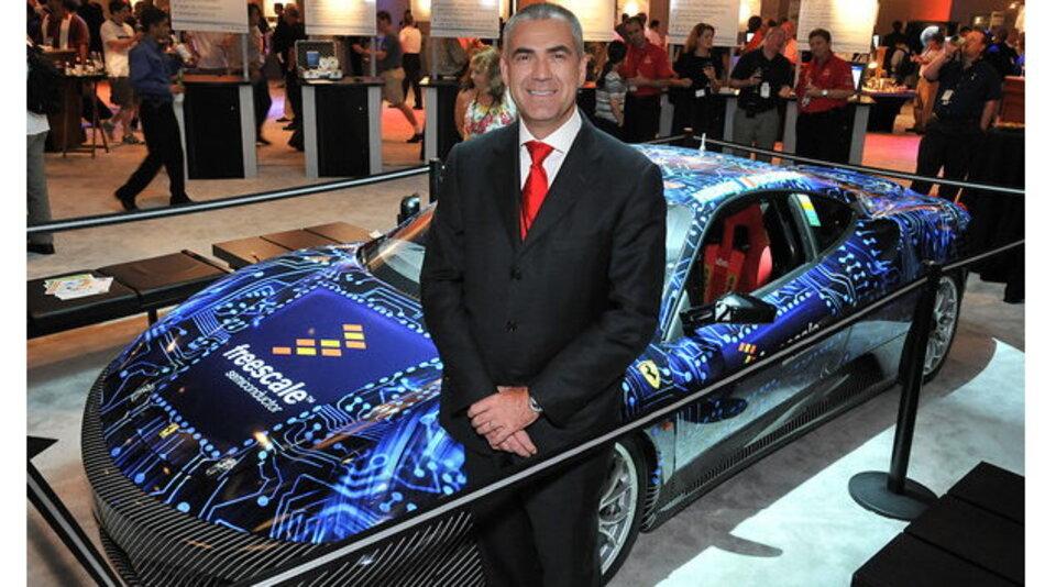 Freescales Ex-CMO Henri Richard posiert bei einem Freescale Technology Forum vor einem seiner Rennwagen.