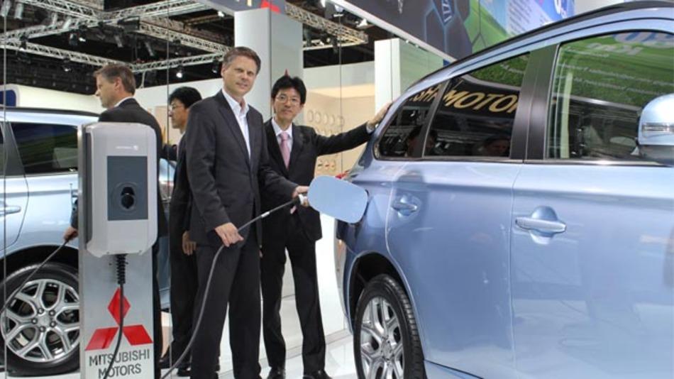 Vattenfall-Projektleiter E-Mobility Ulf Schulte und Mitsubishi-Geschäftsführer Takuro Miki am Outlander PHEV auf der IAA bei der Bekanntgabe des Abkommens.