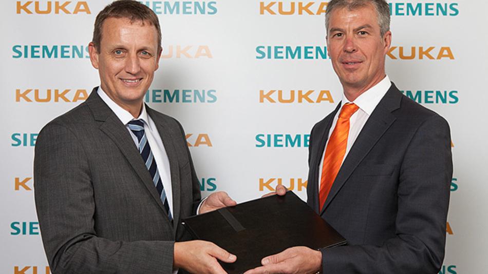 Dr. Robert Neuhauser (links), CEO der Business Unit Motion Control Systems bei Siemens, und Manfred Gundel, CEO der Kuka Roboter GmbH besiegeln die Kooperation mit Handschlag.