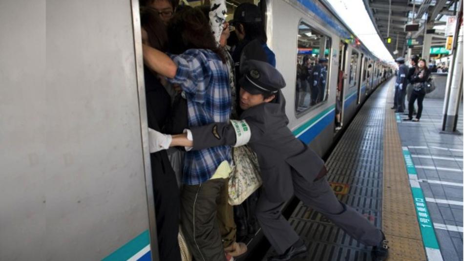 Wenn vermeintlich kein Platz mehr in der U-Bahn ist, wird von offizieller Seite nachgeholfen.