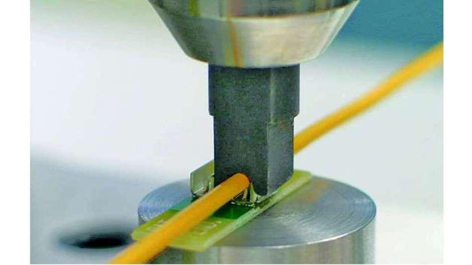 Bild 7: Durch eine Presse wird die Leitung in den Schneid-Crimpanschluss gedrückt und gleichzeitig die Laschen um die Isolierung geklappt