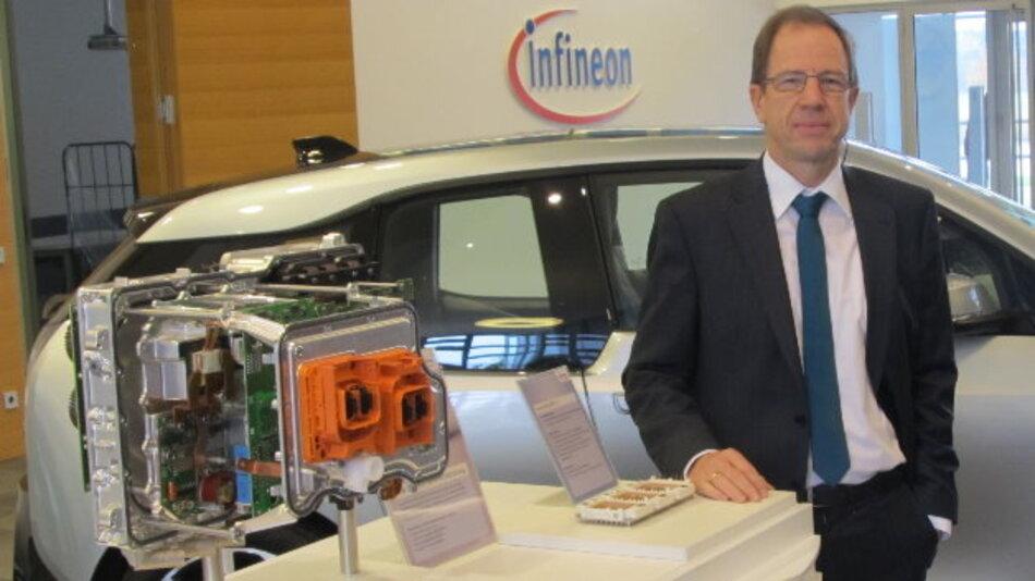 Infineons CEO Dr. Reinhard Ploss mit BMWs E-Car i30, dessen Elektronik maßgeblich von Infineon stammt.