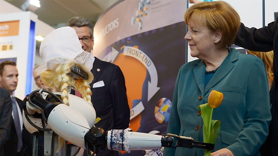 ... überreicht ein niederländisch anmutender Roboter mit blonden Zöpfen der Kanzlerin eine Tulpe.