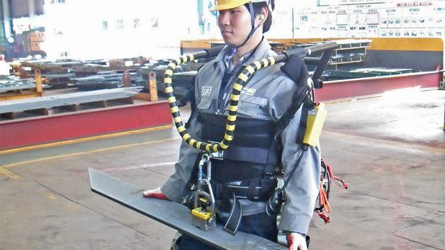 Werftarbeiter im Exoskelett habt ein Metallstück