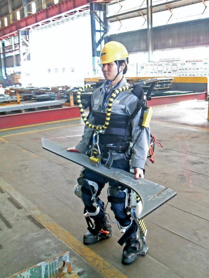 Werftarbeiter im Exoskelett hebt Metallstück