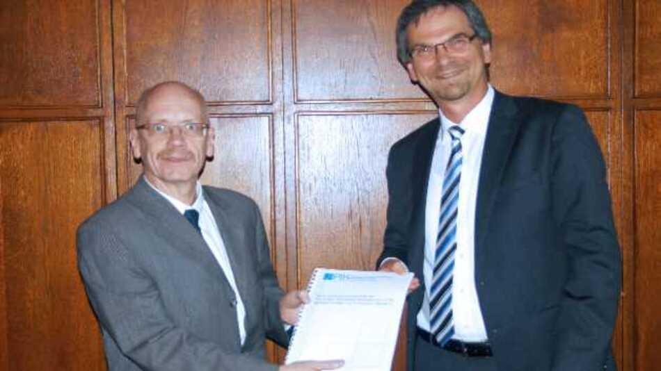 Dr. Roman Schwartz (PTB, rechts) übergibt Dr. Norbert Schultes vom BMWi eine umfangreiche Datensammlung über Aufgaben und Kompetenzen der neu eingerichteten Konformitätsbewertungsstelle.