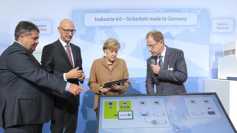 Infineons CEO Dr. Reinhard Ploss erklärt Bundeskanzlerin Merkel die Sicherheitstechnologie. Ganz links Wirtschaftsminister Gabriel, daneben Telekom-CEO Höttges.